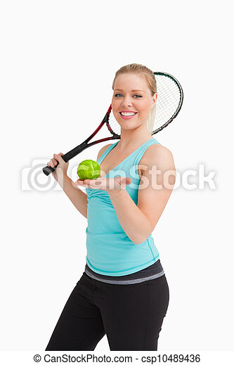 Woman showing a tennis ball in her hand - csp10489436