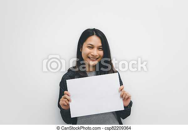 Woman showing blank white paper for copy space - csp82209364