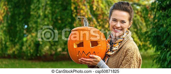 woman showing Halloween pumpkin Jack O'Lantern - csp50871825