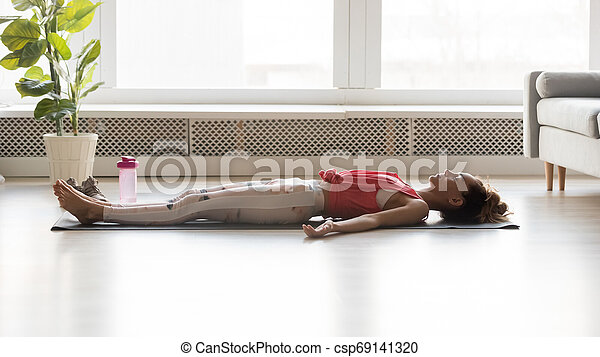 woman side view lying on yoga mat practicing corpse pose