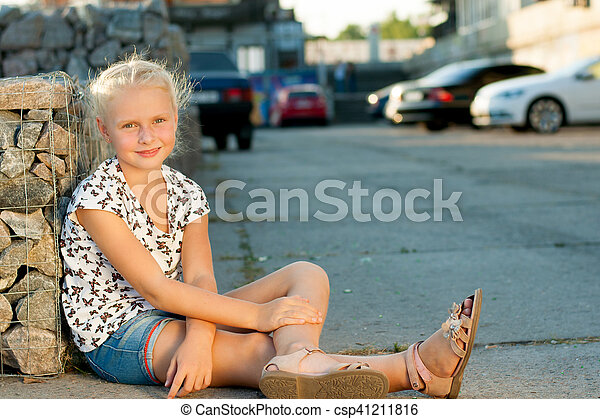 woman sits near a wall on the pavement - csp41211816