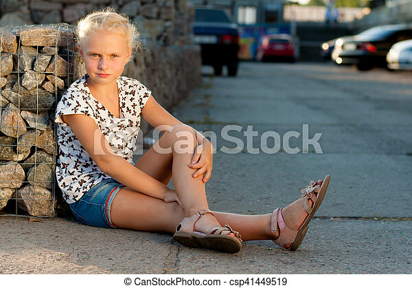 woman sits near a wall on the pavement - csp41449519