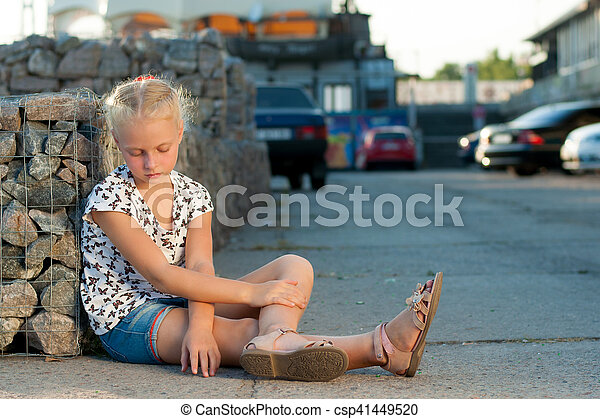 woman sits near a wall on the pavement - csp41449520