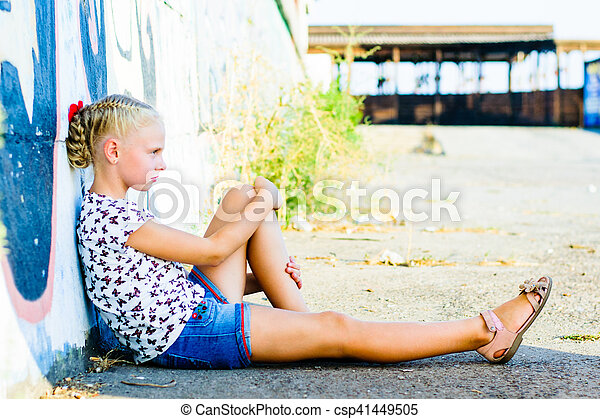 woman sits near a wall on the pavement - csp41449505