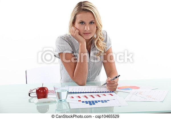 Woman sitting at her desk with statistics - csp10465529