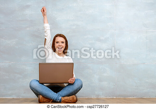 Woman sitting cross-legged pointing up with her arm - csp27726127