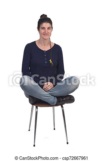 woman sitting in a vintage chair with the lotus pose - csp72667961