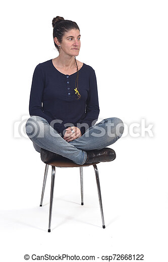 woman sitting in a vintage chair with the lotus pose - csp72668122