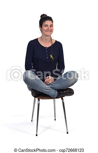woman sitting in a vintage chair with the lotus pose - csp72668123