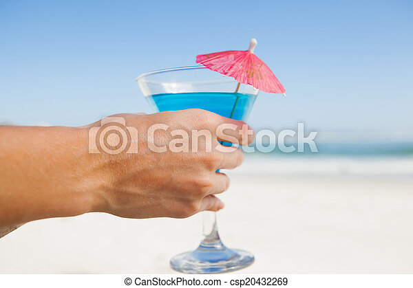 Woman sitting in deck chair with a cocktail at the beach - csp20432269