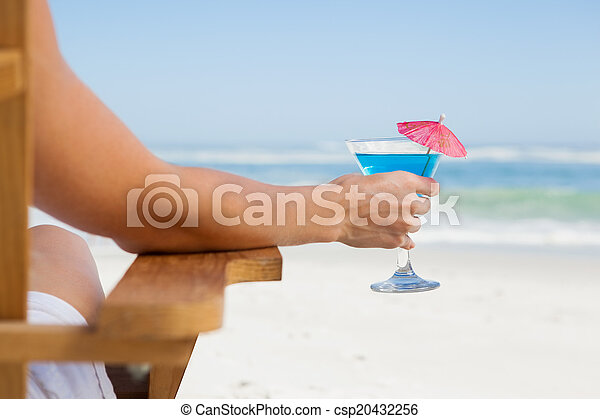 Woman sitting in deck chair with a cocktail at the beach - csp20432256
