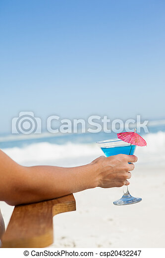 Woman sitting in deck chair with a cocktail at the beach - csp20432247