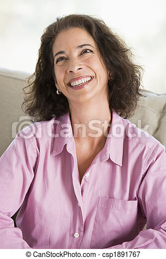 Woman sitting in living room smiling - csp1891767