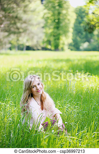 woman sitting in the grass - csp36997213