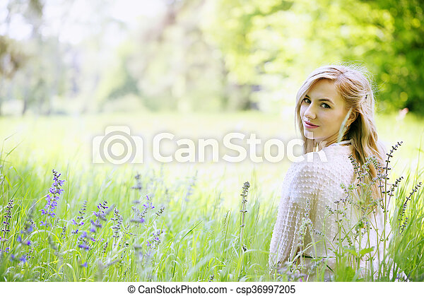 woman sitting in the grass - csp36997205