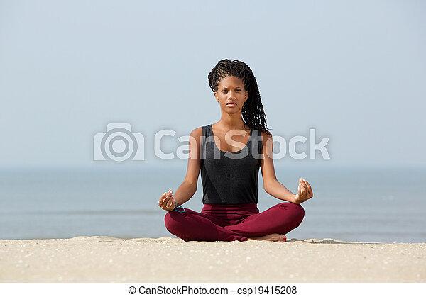 Woman sitting in yoga lotus pose - csp19415208