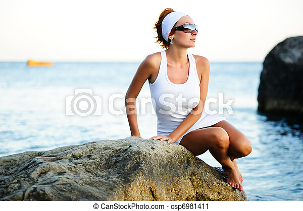 woman sitting on a stone in the sea - csp6981411