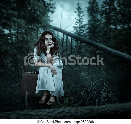 Woman sitting on her suitcase in the forest. - csp42502208