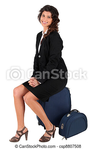 woman sitting on her suitcase - csp8807508