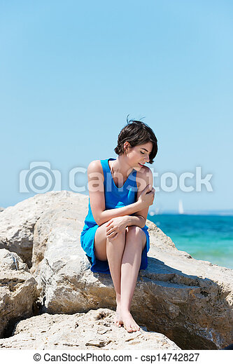 Woman sitting on rocks at the seaside - csp14742827