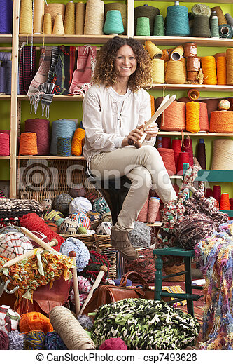 Woman Sitting On Stool Holding Knitting Needles In Front Of Yarn Display - csp7493628