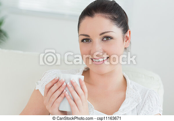 Woman sitting on the couch holding a mug - csp11163671