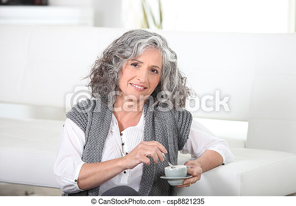 Woman sitting on the floor with a cup of coffee - csp8821235