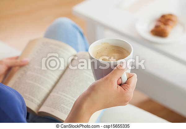 Woman sitting on the sofa reading a book holding her coffee mug - csp15655335