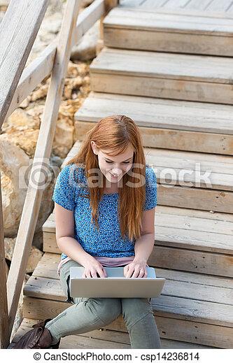 Woman sitting typing on her laptop - csp14236814