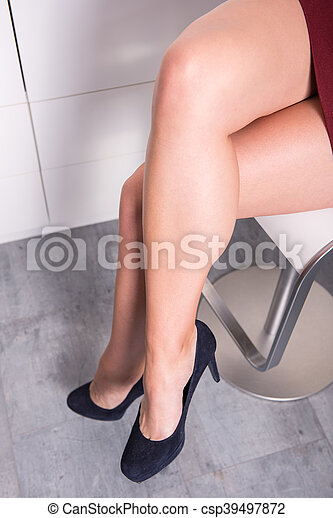 woman sitting with crossed legs on a chair in the office - csp39497872