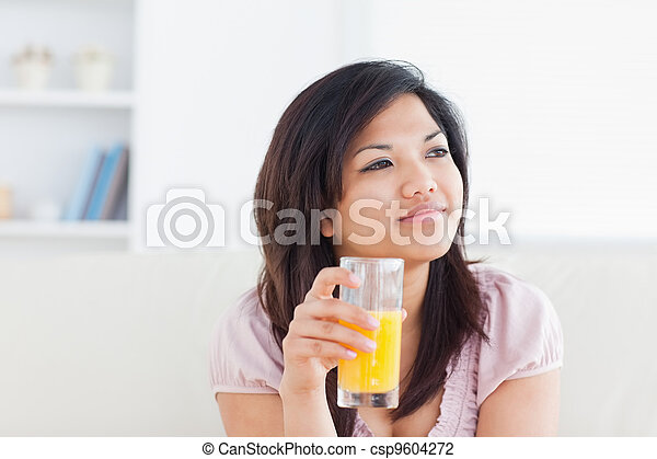 Woman smiling and holding a glass of orange juice - csp9604272
