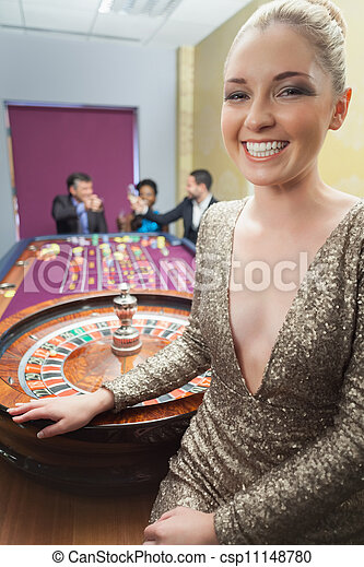 Woman smiling beside roulette wheel - csp11148780