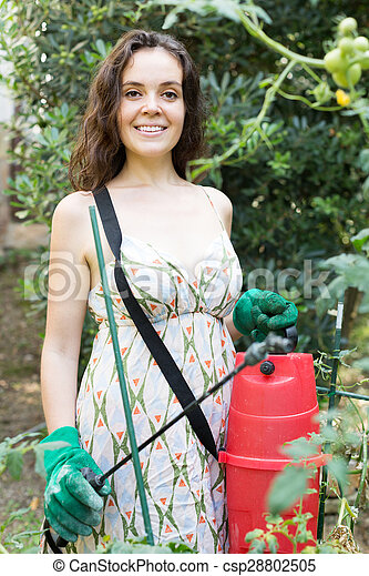 Woman spraying tomato - csp28802505