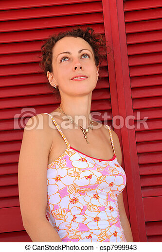 Woman stand near  door from red horizontal jalousies and looks up - csp7999943