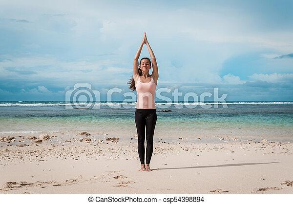 woman standing a namaste yoga pose on the beach sun