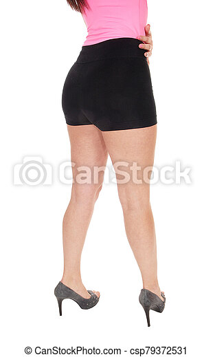 Woman standing from back in black shorts - csp79372531