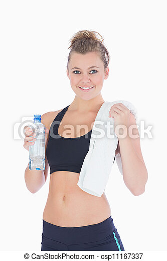 Woman standing holding a bottle and towel in sportswear - csp11167337