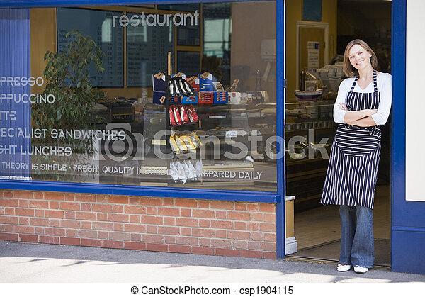 Woman standing in doorway of restaurant smiling - csp1904115
