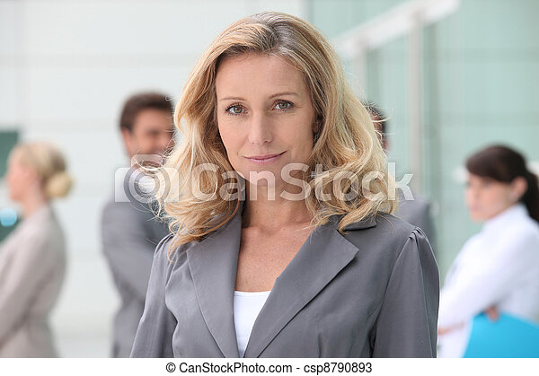 Woman standing in front of her colleagues - csp8790893
