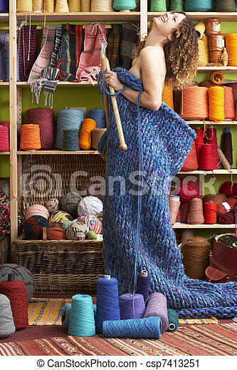 Woman Standing In Knitted Item Standing In Front Of Yarn Display - csp7413251