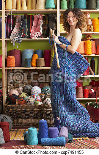 Woman Standing In Knitted Item Standing In Front Of Yarn Display - csp7491455