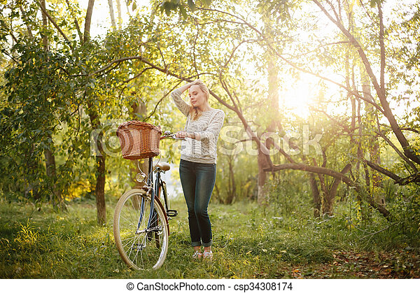 Woman Standing near Vintage Bicycle  - csp34308174