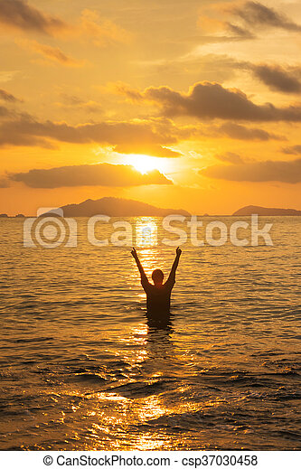 Woman standing on the sea in sunset - csp37030458
