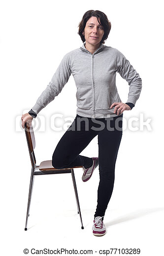 woman standing with a chair in white background - csp77103289