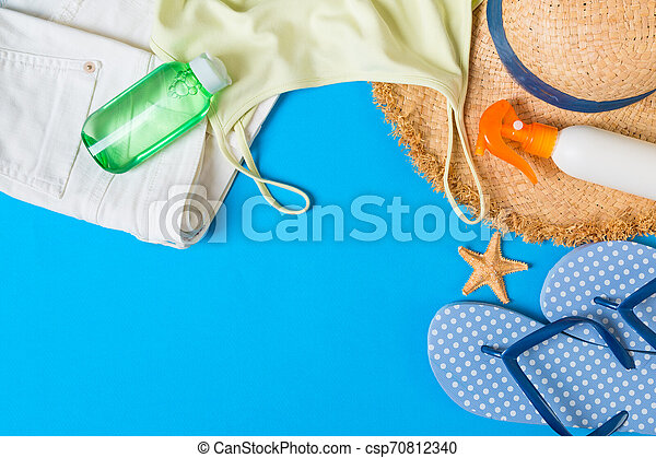 Woman summer outfit top view on blue background. Fashion vacations concept - csp70812340