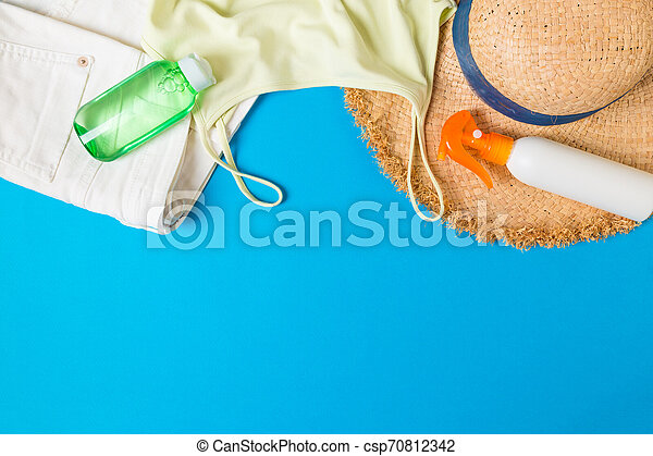 Woman summer outfit top view on blue background. Fashion vacations concept - csp70812342