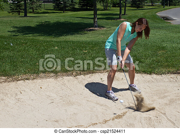 Woman swings at the golf ball caught in the sand trap - csp21524411