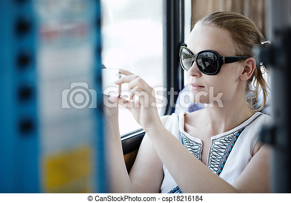 Woman taking pictures at her mobile on a bus - csp18216184
