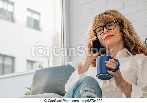 woman talking on the phone at home with cup of coffee - csp92704223