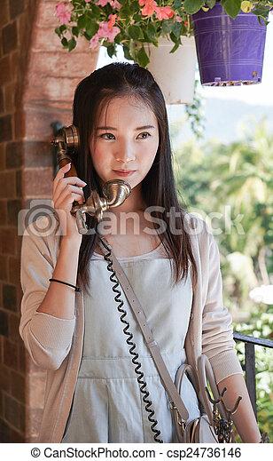 woman talking on vintage telephone - csp24736146